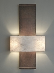 A large architectural wall light Nuit de Chine, by Hannah Woodhouse, is made in aged leather and hand patinated by the artist.  The shade is hand made in eucalyptus paper.